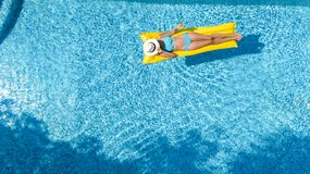 Beautiful young girl relaxing in swimming pool, swims on inflatable mattress and has fun in water on family vacation royalty free stock image