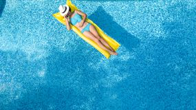 Beautiful young girl relaxing in swimming pool, swims on inflatable mattress and has fun in water on family vacation. Tropical holiday resort, aerial drone royalty free stock photography