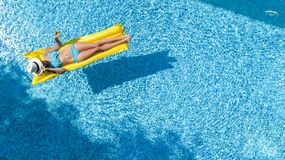 Beautiful young girl relaxing in swimming pool, swims on inflatable mattress and has fun in water on family vacation. Tropical holiday resort, aerial drone stock photos