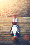 Beautiful young girl resting on a pier on the first day of summer  holding up tablet Royalty Free Stock Photos