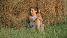 Beautiful young girl resting at stacks of hay at sunset Royalty Free Stock Image