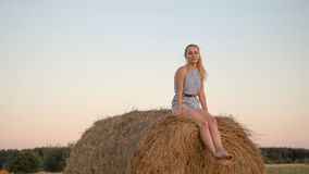 Beautiful young girl resting at stacks of hay at sunset Stock Photography