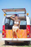 A beautiful young girl in retro look with red lips in a white sw. Imsuit, a bandana and sunglasses is sitting in the car trunk and is looking in the distance Stock Photos