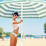A beautiful young girl in retro look with red lips in a white sw. Imsuit, a bandana and sunglasses is holding on the beach umbrella Royalty Free Stock Photo