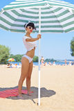 A beautiful young girl in retro look with red lips in a white sw. Imsuit, a bandana and sunglasses is holding on the beach umbrella Royalty Free Stock Photography