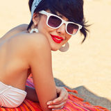 A beautiful young girl in retro look with red lips in a white sw. Imsuit, a bandana and sunglasses is lying on the beach in the shade and looking into the camera Stock Photography