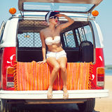 A beautiful young girl in retro look with red lips in a white sw. Imsuit, a bandana and sunglasses is sitting in the car trunk and is looking in the distance Royalty Free Stock Photography
