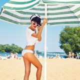 A beautiful young girl in retro look with red lips in a white sw. Imsuit, a bandana and sunglasses is standing on the sand under the beach umbrella Stock Images