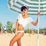 A beautiful young girl in retro look with red lips in a white sw. Imsuit, a bandana and sunglasses is standing under the beach umbrella and is posing for the Stock Images