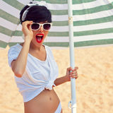 A beautiful young girl in retro look with red lips in a white sw. Imsuit, a bandana and sunglasses is standing under the beach umbrella and is smiling for the Royalty Free Stock Images