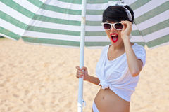 A beautiful young girl in retro look with red lips in a white sw. Imsuit, a bandana and sunglasses is standing under the beach umbrella and is smiling for the Royalty Free Stock Photography