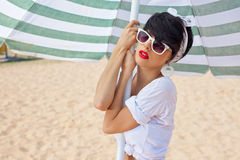 A beautiful young girl in retro look with red lips in a white sw. Imsuit, a bandana and sunglasses is standing under the beach umbrella and is looking into the Stock Photo