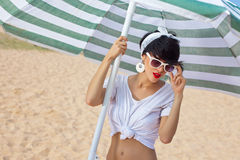 A beautiful young girl in retro look with red lips in a white sw. Imsuit, a bandana and sunglasses is standing under the beach umbrella Stock Photography