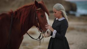 Beautiful young girl in retro style dress posing near horse.Outdoor portrait stock video