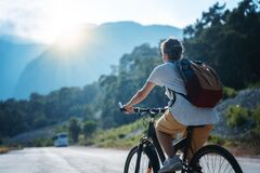 Free Beautiful Young Girl Rides A Bicycle On A Beautiful Mountain Road. Summer Holidays And Cycling, Sports And Outdoor Activities Stock Image - 190336931