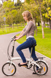 Beautiful young girl riding bicycle in the park Stock Photo