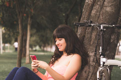 Beautiful young girl riding bicycle in the park Stock Photography