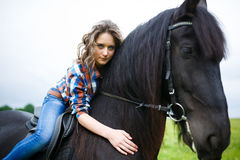 Beautiful young girl riding a horse in countryside Stock Images
