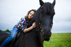 Beautiful young girl riding a horse in countryside Royalty Free Stock Photos
