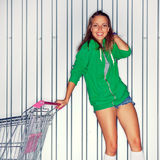 A beautiful young girl in roller skates near supermarket trolley Stock Photography
