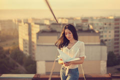 Beautiful young girl at the roof with origami paper crane in hands Royalty Free Stock Image