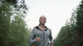 Beautiful young girl running in the park. The blonde is engaged in athletics. stock video