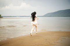 Beautiful young girl runs along the beach Stock Photo