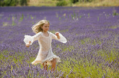 Beautiful young girl runs and jumps in the middle of a purple field of lavender Stock Images