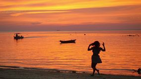 Beautiful young girl runs to the water spin around against the background of sunset on tropical beach. slow motion. Beautiful young girl running on water against stock footage