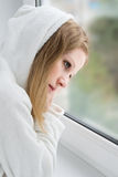 Beautiful young girl is sad at the window Stock Photography