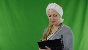 Beautiful young girl  in santa claus hat, she drawing up a list of gifts. stock video
