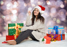 Beautiful young girl in santa hat with big snowflake toy and gif Royalty Free Stock Images