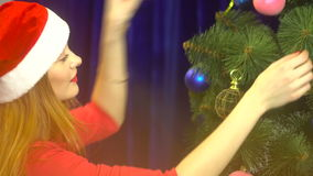 Beautiful young girl in santa hat decorates a christmas tree stock video footage
