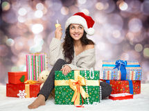 Beautiful young girl in santa hat with  glass of champagne and gift boxes Stock Photo