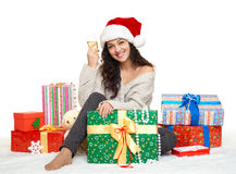 Beautiful young girl in santa hat with a glass of champagne and gift boxes Stock Images