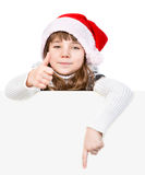 Beautiful young girl with santa hat standing behind white board. royalty free stock photos