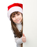 Beautiful young girl with santa hat standing behind white board  on white Stock Photography