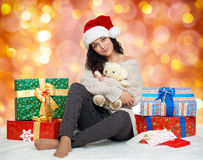 Beautiful young girl in santa hat with teddy bear toy and gift boxes, colorful bokeh background Stock Image