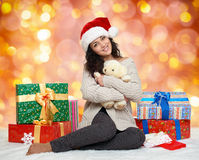 Beautiful young girl in santa hat with teddy bear toy and gift boxes, colorful bokeh background Stock Photography
