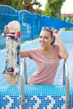 A beautiful young girl with a scateboard on the pool ladder Stock Photo