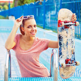 A beautiful young girl with a scateboard on the pool ladder Royalty Free Stock Image