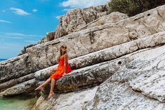 Beautiful young girl by the sea. Woman in a red dress on the beach. Seaside vacation. Rocky terrain royalty free stock photography