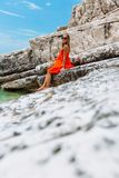 Beautiful young girl by the sea. Woman in a red dress on the beach. Seaside vacation. Rocky terrain royalty free stock photo