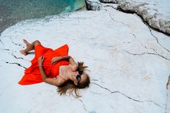 Beautiful young girl by the sea. Woman in a red dress on the beach. Seaside vacation. Rocky terrain royalty free stock image
