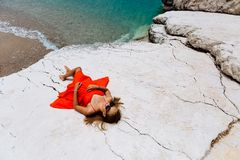 Beautiful young girl by the sea. Woman in a red dress on the beach. Seaside vacation. Rocky terrain royalty free stock photos
