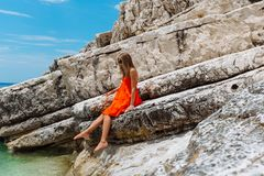 Beautiful young girl by the sea. Woman in a red dress on the beach. Seaside vacation. Rocky terrain stock images