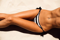 Beautiful young girl in a sexy bikini rests on the sand of a tro. Skinny young beautiful woman in a striped black and white bikini sunbathing on the soft sandy Royalty Free Stock Photo