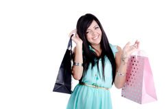Beautiful young girl with shopping bags. Beautiful young girl in studio standing holding shpping bags -and smiling Royalty Free Stock Photography