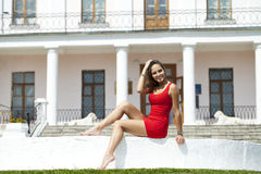 Beautiful young girl in short red dress sitting on the white sto Royalty Free Stock Photos