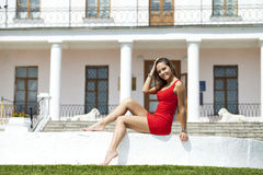 Beautiful young girl in short red dress sitting on the white sto Stock Images